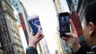 FILE PHOTO: A company executive photographs a Luckin Coffee cup during the company's IPO at the Nasdaq Market site in New York,…