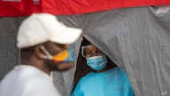A health worker wearing personnel protection equipment, looks on during a COVID screening and testing campaign