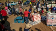 People affected by the coronavirus economic downturn, receive food donations at the Iterileng informal settlement near Laudium, southwest of Pretoria, South Africa, May 20, 2020.