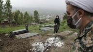 A woman wearing a mask and gloves prays at the grave of her mother, who died from the new coronavirus, at a cemetery in the outs