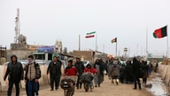 FILE - Afghans return to Afghanistan at the Islam Qala border with Iran, in the western Herat Province, Feb. 20, 2019.