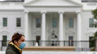 FILE - A woman wearing a face mask walks past the White House in Washington, April 1, 2020.