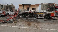 FILE - Damaged vehicles and buildings are seen at Mitiga airport after it was hit by shelling, in Tripoli, Libya, May 10, 2020.