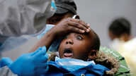 A young girl reacts as a medical worker takes a swab during mass tasting in an effort to fight against the spread of the coronavirus disease (COVID-19) in the Kawangware neighborhood of Nairobi, Kenya, May 2, 2020.