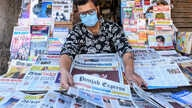 A vendor wearing a facemask amid concerns over the spread of the COVID-19 novel coronavirus, displays newspapers at his stall in Amritsar on March 20, 2020.