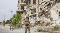 Turkish soldiers patrol along a road past destroyed buildings atop the Arbaeen hill overlooking Ariha in the southern…