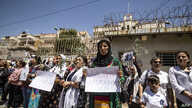 Displaced Syrians from the northern city of Afrin, hold placards during a demonstration to condemn violations by local Turkish…