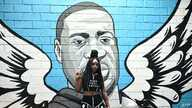 A woman raises her fist in front of a mural of George Floyd in Houston, Texas on June 8, 2020. - George Floyd, the 46-year-old…