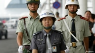 Chinese police patrol the Baiyun International Airport in Guangzhou August 5, 2004.