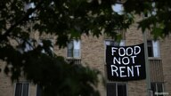 Makeshift sheets displaying messages of protest contesting the ability to pay for rent hang in the window of an apartment…