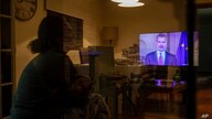 FILE - A woman watches the speech of King Felipe VI of Spain on television, in Bustarviejo, outskirts of Madrid, March 18, 2020.