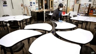 Des Moines Public School employee Sam Teah sanitizes a desk in a classroom at Central Campus high school, Thursday, March 19,…
