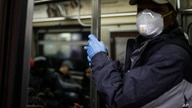FILE - A New York subway rider wears protective gloves and a mask while holding onto a pole, March 19, 2020.