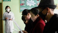 FILE - People review information explaining the COVID-19 coronavirus at the Phyongchon District People's Hospital in Pyongyang, North Korea, April, 1, 2020.