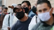 Workers wearing face masks amid the new coronavirus line up to enter the Corabastos market, one of Latin America's largest food…