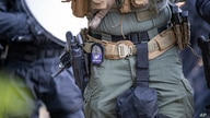 The badge on an Arlington County Police officer is seen as he aims a less lethal weapon as demonstrators are moved back after…