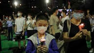 Participants hold candles during a vigil for the victims of the 1989 Tiananmen Square Massacre at Victoria Park in HK