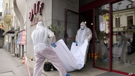 Forensic workers carry the body of Gholamreza Mansouri from a hotel downtown Bucharest, Romania, Friday, June 19, 2020…