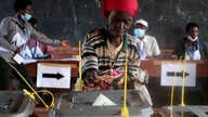 A voter casts her ballot at a polling station during the presidential, legislative and communal council elections, under the…