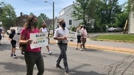 """Julia Young, marching with her father Malcolm, in an Arlington, Virginia, """"Say Their Names"""" protest against police brutality. (VOA/Carolyn Presutti)"""