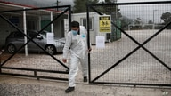 A man wearing a protective suit to protect against coronavirus leaves a migrant facility at Malakasa village, north of Athens, April 5, 2020.