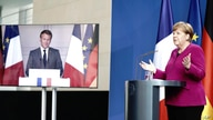 FILE - German Chancellor Angela Merkel talks to French President Emmanuel Macron, connected by video, during a press conference after a joint video conference in Berlin, Germany, May 18, 2020.