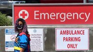 A woman wears a face-covering while walking past a sign leading to the Emergency section at the Los Angeles County+USC Medical…