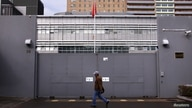 A man walks past the front gate of the Chinese consulate in Sydney, Australia, July 23, 2015. Australian police arrested eight…