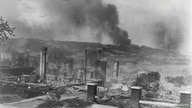 Smoke rises from the ruins of African Americans' homes following the race massacre in Tulsa, Oklahoma in 1921.     Alvin C…