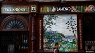 A man wearing a protective mask walks past a closed flamenco bar, amid the coronavirus disease (COVID-19) outbreak, in Madrid,…