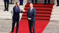 Former French Prime Minister Edouard Philippe applauds newly-appointed Prime Minister Jean Castex in the courtyard of the…