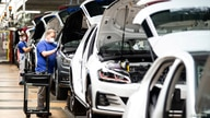FILE PHOTO: A worker wears a protective mask at the Volkswagen assembly line after VW re-starts Europe's largest car factory…