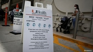 FILE - A sign is seen at the entrance of Jackson Memorial Hospital, as Miami-Dade County eases lockdown.