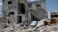 FILE PHOTO: Saher al-Ali's family members stand inside their damaged house in the rebel-held town of Nairab,  Idlib region,…