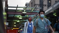 Healthcare workers walk through the Texas Medical Center during a shift change as cases of the coronavirus disease (COVID-19).