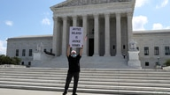 Demonstrator Bill Christeson holds a sign outside the U.S. Supreme Court, where justices ruled that a prosecutor in New York.