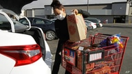 Instacart worker Saori Okawa loads groceries into her car for home delivery in San Leandro, Calif., July 1, 2020. Okawa is one of an estimated 1.5 million so-called gig workers who make a living driving people to airports, picking out produce at grocery stores or providing child care for working parents.