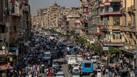 FILE - In this April 14, 2020 file photo, people crowd a street a few hours ahead of curfew in Cairo, Egypt. As Egyptian…