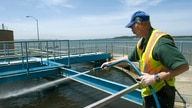 FILE - Robert Newman hoses off a portion of sewage treatment Plant No. 2 in Coos Bay, Ore.