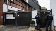 Police officers are standing in front of an apartment building in Erfurt, Germany, Jan. 23, 2020. Germany's top security official has announced a ban on the neo-Nazi group 'Combat 18' Deutschland.
