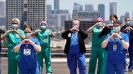 FILE - Healthcare professionals pose a group photo on a helipad at Memorial Hermann Hospital after the U.S. Navy's Blue Angels flyover of the Medical Center Wednesday, May 6, 2020, in Houston.