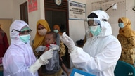 Health workers in protective gear prepare the measles vaccine to be given to baby at a community health center in Tangerang, Indonesia, May 12, 2020.