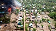 FILE - A fire burns in the predominantly ethnic Rakhine village of Let Kar in Rakhine State's Mrauk-U township, western Myanmar, May 16, 2020.