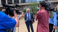 FILE - Defense attorney Earl Gray, center, talks to reporters outside court in downtown Minneapolis after his client, former Minneapolis police Officer Thomas Lane, made his first court appearance in the death of George Floyd, June 4, 2020.