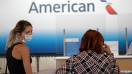In this June 16, 2020 file photo travelers wear masks as they wait at the American Airlines ticket counter at O'Hare…