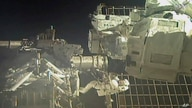 In this image taken from NASA video, commander Chris Cassidy, right, and NASA astronaut Bob Behnken perform their second spacewalk in under a week, July 1, 2020, to replace old batteries outside the International Space Station.