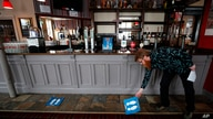 Owner Are Kjetil Kolltveit from Norway places markers for social distancing on the front of the bar at the Chandos Arms pub in London, July 1, 2020.