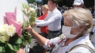People place flowers on vans  as hundreds of people turned out in Sarajevo's main street, July 9, 2020, to pay respects to eight victims of the Srebrenica massacre as three white vans carried their coffins to a final resting place.