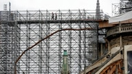 Workers walk through a scaffolding at Notre Dame cathedral, July 10, 2020 in Paris. Notre Dame Cathedral will be rebuilt just the way it stood before last year's devastating fire.