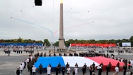Members of medical staff pose with the French flag as they take part in the annual Bastille Day military ceremony on the Place de la Concorde in Paris, July 14, 2020.